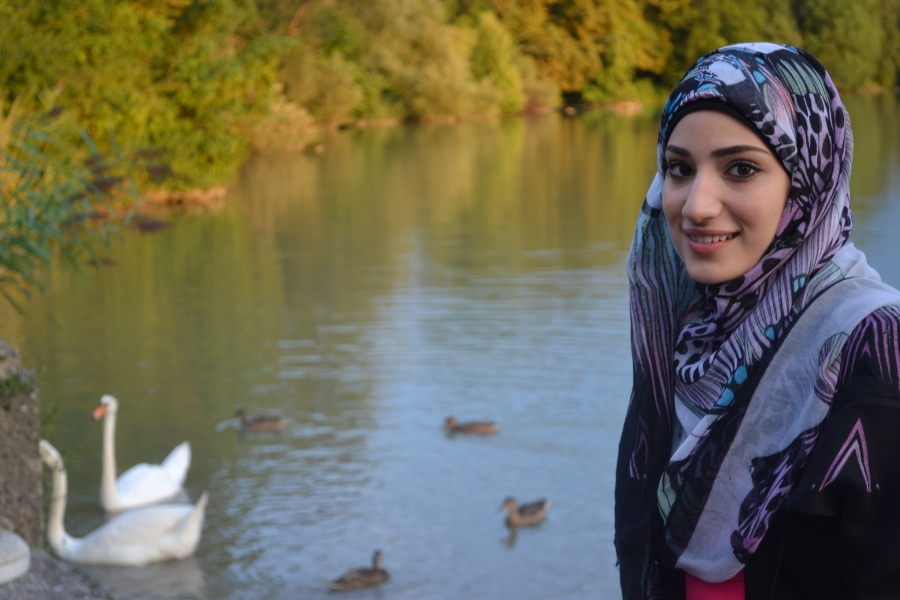 Woman_standing_in_front_of_river_with_swans